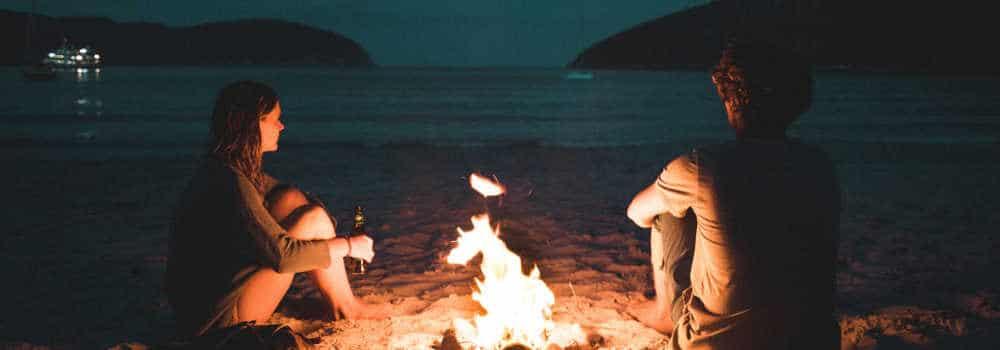 couple sitting with a bonfire